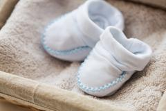 close up of baby bootees for newborn boy in basket - stock photo