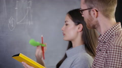 4K Young man & woman in discussion brainstorming with sticky notes on blackboard - stock footage