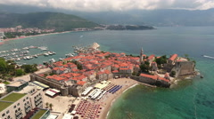 Camera lifting up over well preserved medieval walled town of Budva. Montenegro Stock Footage