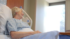 Doctor Talks To Senior Patient In Hospital Bed Shot On R3D Stock Footage