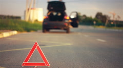 Young woman feeling frustrated over flat tyre, red warning triangle on the road Stock Footage