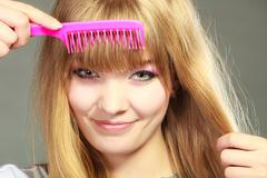 Closeup woman combing her fringe with pink comb Stock Photos