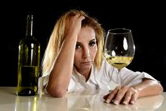 Drunk blond woman alone in wasted depressed expression looking thoughtful wit Stock Photos