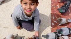 Little boy feeding pigeons in Placa de Catalunya, Barcelona, slow motion Stock Footage
