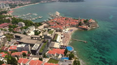 Camera down over Mogren beach and mediaval walled town of Budva city. Montenegro Stock Footage
