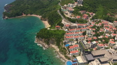Flying over coastal road and Mogren beach nested beneath the cliffs. The Budva Stock Footage