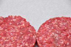 Raw meat burgers for hamburgers on parchment - stock photo