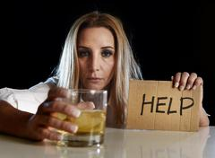 Drunk alcoholic blond woman drinking whiskey glass asking for help Stock Photos