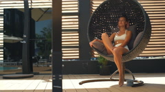 Beautiful female in bikini relaxing in rattan round chair slow motion Stock Footage