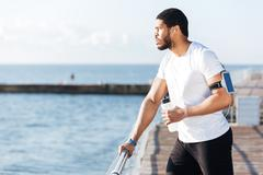 Sportsman listening to music and drinking water on pier - stock photo