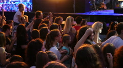 Crowd people fan spectators dancing jumping by concert stage in lumiere flash Stock Footage