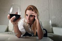 Blond sad and wasted alcoholic woman sitting at home sofa couch drinking Stock Photos