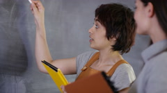 4K Young women in discussion, drawing graph on blackboard.  - stock footage