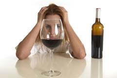 caucasian blond wasted and depressed alcoholic woman drinking red wine glass - stock photo