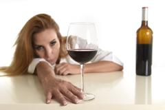Caucasian blond wasted and depressed alcoholic woman drinking red wine glass Stock Photos