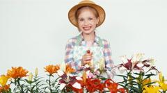Close up portrait flower-girl in hat using sprinkler and sprinkling flowers - stock footage