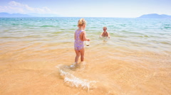 Little Girl Walks in Shallow Water to Mother in Azure Sea Stock Footage