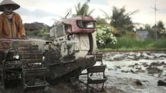 Balinese man riding old wheel plow in the rice field near Ubud Bali Stock Footage