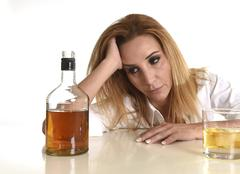 caucasian blond wasted and depressed alcoholic woman drinking scotch whiskey - stock photo