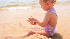 Blond Little Girl Builds Sand Castle on Beach of Azure Sea Stock Footage