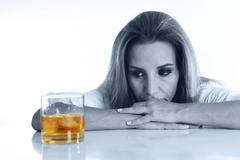 Caucasian blond wasted and depressed alcoholic woman drinking scotch whiskey Stock Photos