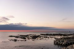 Rock beach near tranquil sea at sunrise Stock Photos