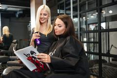 Woman discussing haircut with her hairdresser in the hairdressing salon - stock photo