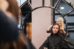 Mirror reflection of young woman getting her hairdo by stylist - stock photo