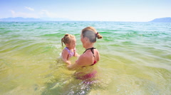 Mother Tosses High up Little Daughter in Azure Sea Stock Footage