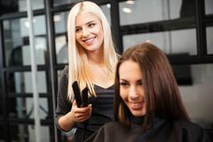 Stylist with styling iron straightening woman hair at salon - stock photo
