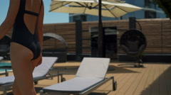 close up back view of female in maillot walking along the pool slow motion - stock footage