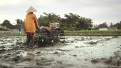 Farmer working with a motor plow in a wet rice field near Ubud, Bali Stock Footage
