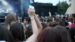 Teenager girls fan spectators in a crowd raise sway hands enjoying music Stock Footage