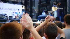 Cheering crowd people fan spectators clapping hands by concert stage slow motion - stock footage