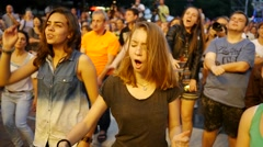 Teenage girl fan spectator cheerfully dancing in people crowd enjoying concert Stock Footage