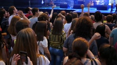 People crowd fan spectators by concert stage enjoy music raise up hands slow  Stock Footage