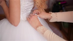 Bridesmaid is lacing white wedding dress for beautiful bride,preparing wedding Stock Footage