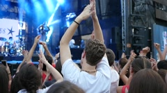 Cheering crowd people fan spectators clapping hands by concert stage slow motion Stock Footage