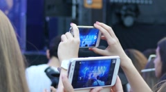 Spectator fan shooting video via smart phone at a music concert by a stage Stock Footage