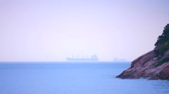 Cargo freighter ship sailing, moving at ocean horizon sky in hazy sea Stock Footage