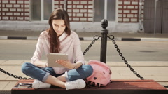 Young beautiful student girl using a tablet computer outside. Pretty teen woman - stock footage