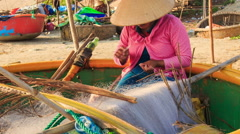 Closeup Woman Sits in Round Boat Mends Fishing Nets on Beach Stock Footage