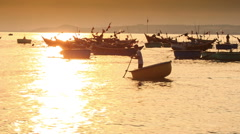 Man Rows Round Fishing Boat among Boats at Sunset in Vietnam Stock Footage