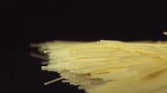 SLOW MOTION: A spaghetti fall on a black table - side view Stock Footage