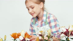Close up portrait flower-girl sniffing flowers and smiling at camera on white Stock Footage