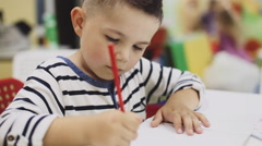 Little boy drawing with colored pencils on paper Stock Footage