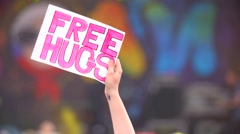 Young girl holds free hugs poster at concert and dance Stock Footage