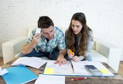 Young worried couple at home couch doing domestic debt accounting tax paperwork Stock Photos