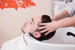 Handsome man in hairdressing saloon - stock photo