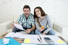 Young happy relaxed couple at home sofa couch doing domestic debt accounting Stock Photos